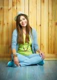 Muchacha del smilingl de Beautifu que se sienta contra fondo de madera en una f Imagen de archivo