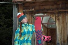Muchacha del Snowboarder que descansa sobre la terraza de una casa de madera Foto de archivo