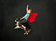 Muchacha del super héroe que monta su perro foto de archivo libre de regalías
