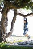 Muchacha del tween que hace pivotar de la ramificación de árbol imágenes de archivo libres de regalías