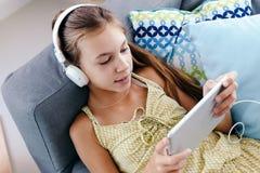 Muchacha del tween que se relaja en el sofá en casa Fotos de archivo libres de regalías