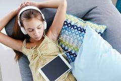Muchacha del tween que se relaja en el sofá en casa Imágenes de archivo libres de regalías