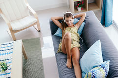 Muchacha del tween que se relaja en el sofá en casa Fotos de archivo
