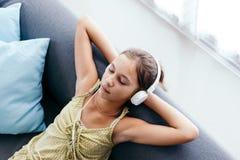 Muchacha del tween que se relaja en el sofá en casa Foto de archivo libre de regalías