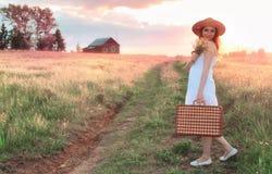 Muchacha del verano de la puesta del sol en un campo con las flores Imagen de archivo libre de regalías