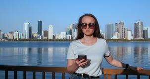 Muchacha del verano en el fondo de una situación sonriente de la ciudad grande con un smartphone metrajes