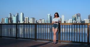 Muchacha del verano en el fondo de una situaci?n sonriente de la ciudad grande con un smartphone almacen de metraje de vídeo