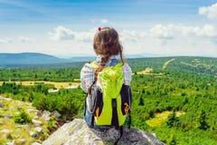 Muchacha del viaje de los jóvenes que se sienta en la montaña de la roca con la mochila, con referencia a Fotos de archivo