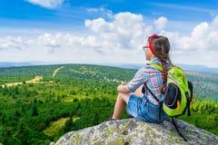 Muchacha del viaje de los jóvenes que se sienta en la montaña de la roca con la mochila, con referencia a Imagenes de archivo