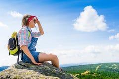 Muchacha del viaje de los jóvenes que se sienta en la montaña de la roca con la mochila, con referencia a Imágenes de archivo libres de regalías