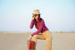 Muchacha del viajero con la maleta que mira en prismáticos foto de archivo libre de regalías