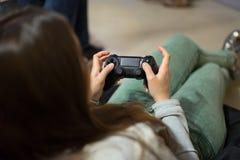 Muchacha del videojugador que juega a los videojuegos con la palanca de mando que se sienta en silla del puf Foto de archivo