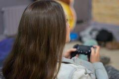 Muchacha del videojugador que juega a los videojuegos con la palanca de mando que se sienta en silla del puf Fotografía de archivo