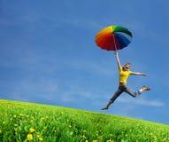 Muchacha del vuelo con el paraguas colorido en el bl azul Imágenes de archivo libres de regalías