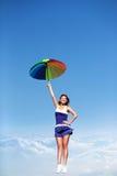 Muchacha del vuelo con el paraguas colorido en el cielo azul Fotos de archivo libres de regalías