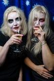 Muchacha del zombi con los ojos morados y una boca sangrienta en Halloween Foto de archivo