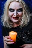 Muchacha del zombi con los ojos morados y una boca sangrienta en Halloween Imágenes de archivo libres de regalías