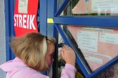 Muchacha delante de la guardería cerrada debido a huelga Fotos de archivo libres de regalías