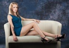 Muchacha delgada atractiva que se sienta en el diván Fotografía de archivo