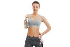 Muchacha delgada de la aptitud que sostiene una botella de agua mineral y de miradas delanteras Foto de archivo libre de regalías