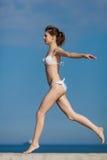 Muchacha delgada descalza en el funcionamiento blanco del bikini fotos de archivo libres de regalías