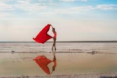 Muchacha delgada en el lago de sal de Elton, región de Stalingrad, Rusia Lago Elton Una muchacha en un bañador y un pareo rojos,  fotografía de archivo