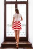Muchacha delgada en la falda corta que sale al balcón Foto de archivo libre de regalías