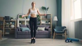Muchacha delgada en las polainas y la cuerda de salto superior en casa concentradas en actividad almacen de metraje de vídeo