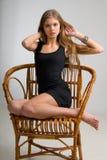 Muchacha delgada en una silla Imagen de archivo libre de regalías