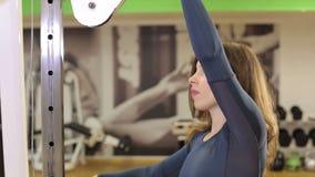 Muchacha delgada fuerte que hace el entrenamiento de la fuerza en el gimnasio entre muchos simuladores almacen de video