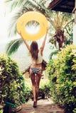 Muchacha delgada hermosa en bikini rayado atractivo que camina abajo del stai Foto de archivo