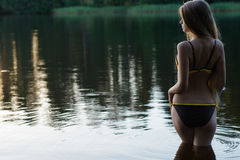 Muchacha delgada hermosa en el traje de baño que se coloca en el agua, visión trasera Foto de archivo