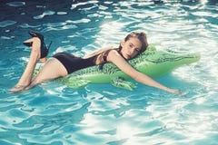 muchacha delgada hermosa en un traje de ba?o Flotaci?n en una piscina inflable del cocodrilo de la playa verde grande fotografía de archivo