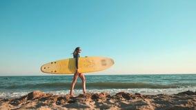 Muchacha delgada hermosa que camina en la playa, sosteniendo la tabla hawaiana Funcionamientos por la tarde durante puesta del so almacen de video
