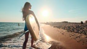 Muchacha delgada hermosa que camina en la playa, sosteniendo la tabla hawaiana Funcionamientos por la tarde durante puesta del so metrajes