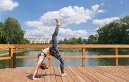 Muchacha delgada joven en el desgaste gris del deporte que hace yoga en el puente Chica joven flexible con el pelo rojo fotos de archivo