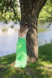 Muchacha delgada por el árbol Fotos de archivo