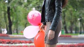 Muchacha delgada que camina abajo de la calle con los globos a disposición almacen de metraje de vídeo