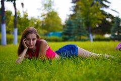 Muchacha delgada que miente en hierba verde en un jardín enorme Foto de archivo libre de regalías