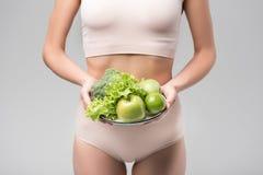 Muchacha delgada que muestra la comida sana Imágenes de archivo libres de regalías