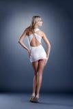 Muchacha delgada que presenta en vestido corto, de nuevo a cámara Imagen de archivo