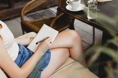 Muchacha delgada que se sienta en el sofá de cuero beige y el dibujo Imagen de archivo