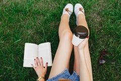 Muchacha delgada que se sienta en la hierba con la taza de café Foto de archivo