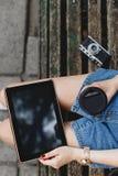 Muchacha delgada que se sienta en un banco de madera oscuro Fotos de archivo