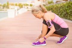 Muchacha deportiva activa que ata los zapatos antes de entrenamiento de la mañana Imagen de archivo