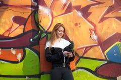 Muchacha deportiva al aire libre usando su teléfono móvil Imágenes de archivo libres de regalías