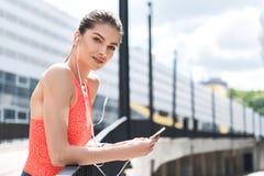 Muchacha deportiva alegre que usa al jugador del smartphone después de ejercitar Imagen de archivo libre de regalías