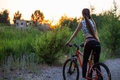 Muchacha deportiva atractiva con el pelo largo en una bicicleta en puesta del sol foto de archivo libre de regalías