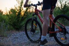 Muchacha deportiva atractiva con el pelo largo en una bicicleta en puesta del sol imagenes de archivo