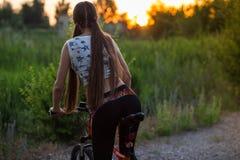 Muchacha deportiva atractiva con el pelo largo en una bicicleta en puesta del sol fotografía de archivo libre de regalías